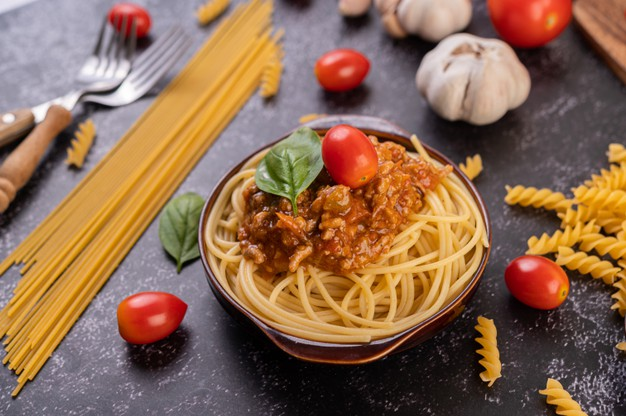 Spaghetti saute in a gray plate with tomatoes and basil Free Photo