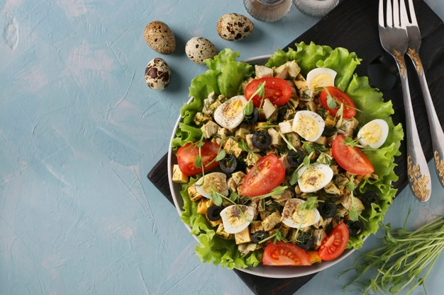 Premium Photo | Organic salad with chicken, cherry tomatoes, quail eggs, black olives and microgreens against on light blue surface, healthy eating day, top view